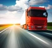 7112453-red-camion-sur-route-asphaltee-floue-sur-fond-bleu-ciel-nuageux